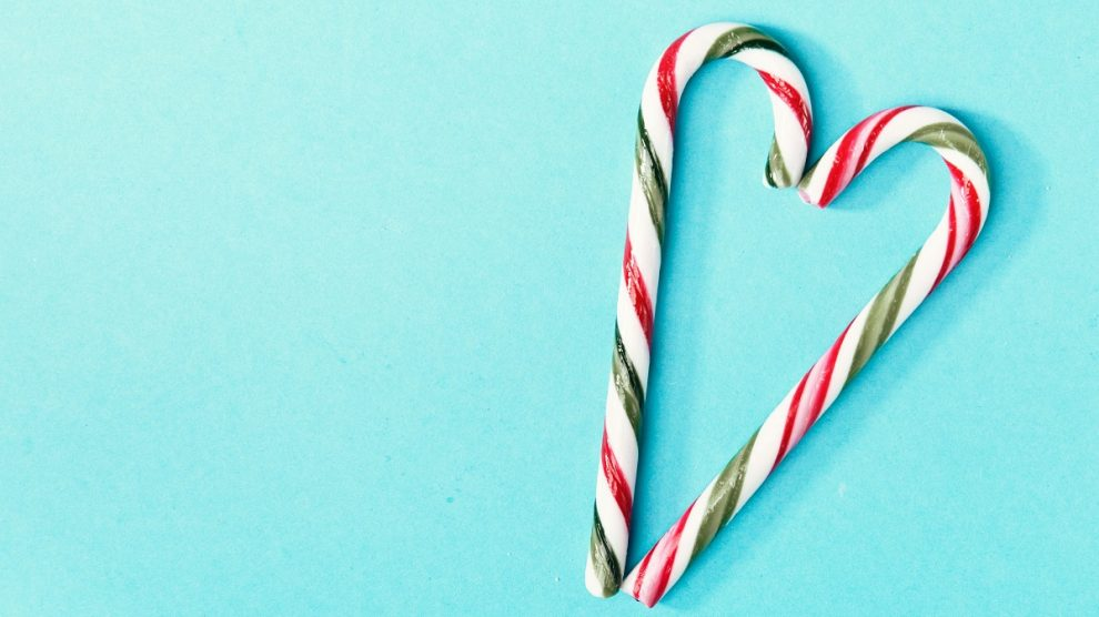 Top view of two colorful candy canes arranged in heart on blue background.
